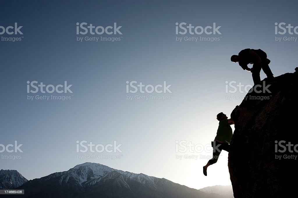 Silhouette of climbers on a rock royalty-free stock photo