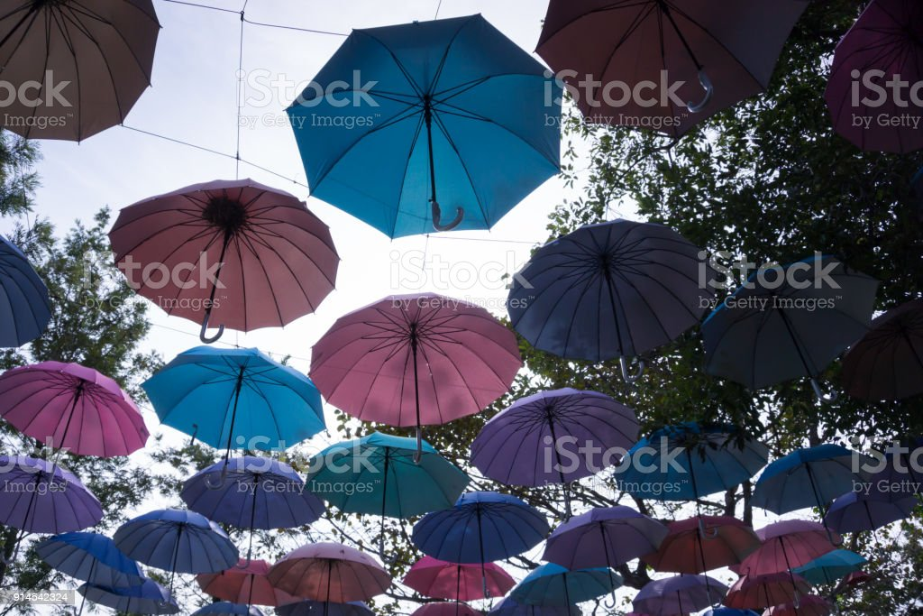 Silhouette of colorful umbrellas hanging above the street stock photo