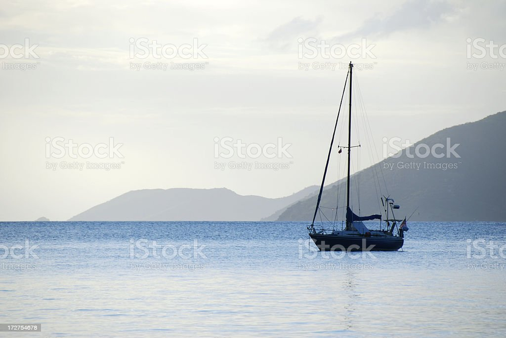 Silhouette of Come Sail Away Sailboat in Calm Island Harbor royalty-free stock photo