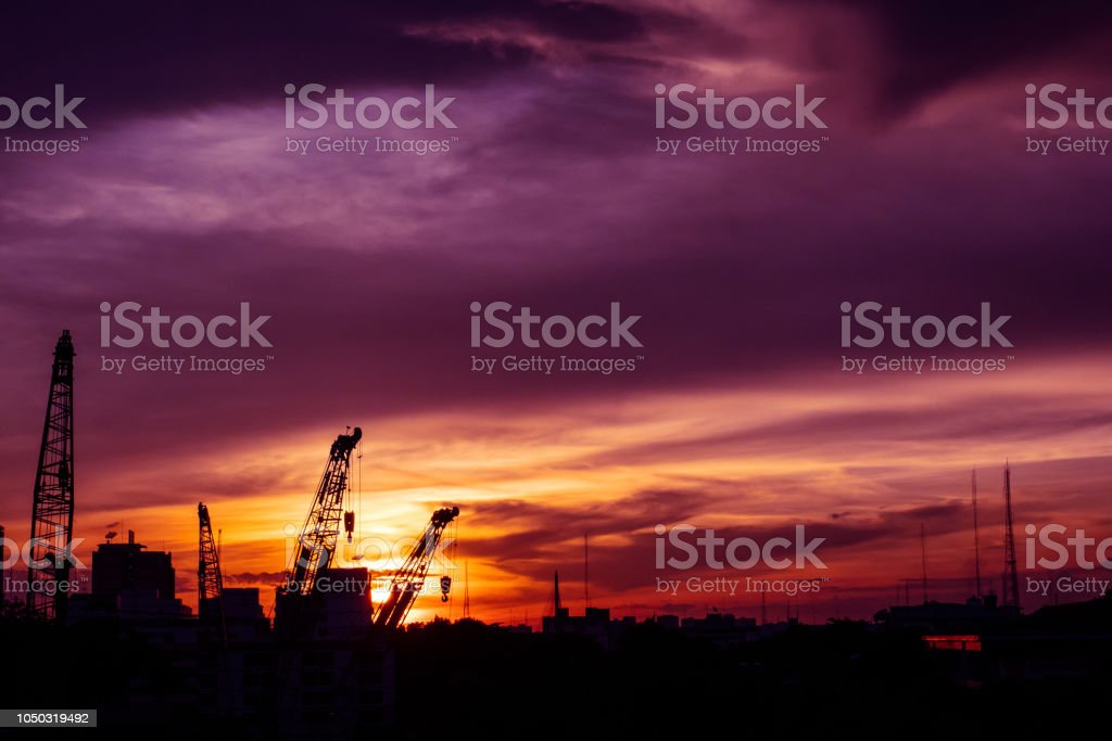 Silhouette of construction site with colorful sunset sky stock photo