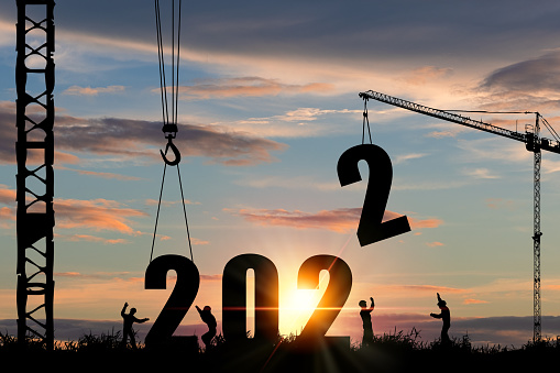 Silhouette of construction worker with crane and cloudy sky for preparation of welcome 2022 new year party and change new business.