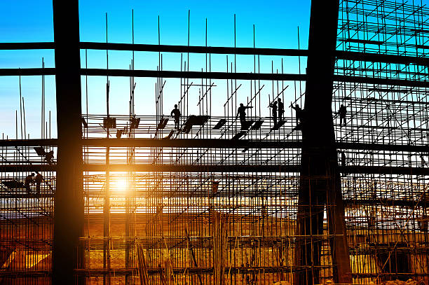 Silhouette of construction workers on scaffolding Construction workers working on scaffolding, dusk picture. scaffolding stock pictures, royalty-free photos & images