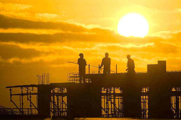 Silhouette of construction workers on site at sunset stock photo
