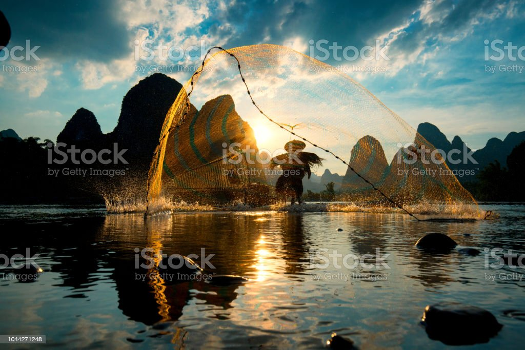 Silhouette der Kormoran Fischer mit Netz auf dem alten Bambus-Boot – Foto