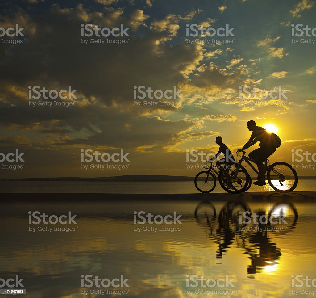 silhouette of couple cyclist at sunset with reflection on water stock photo