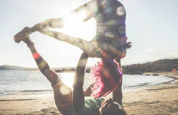 Silhouette du couple faisant acro yoga en plein air sur la plage - femme et homme, formation sur temps au concept de mode de vie sain - Focus sur le corps - coucher de soleil - filtre de tonalités de couleur soleil du soir - Photo