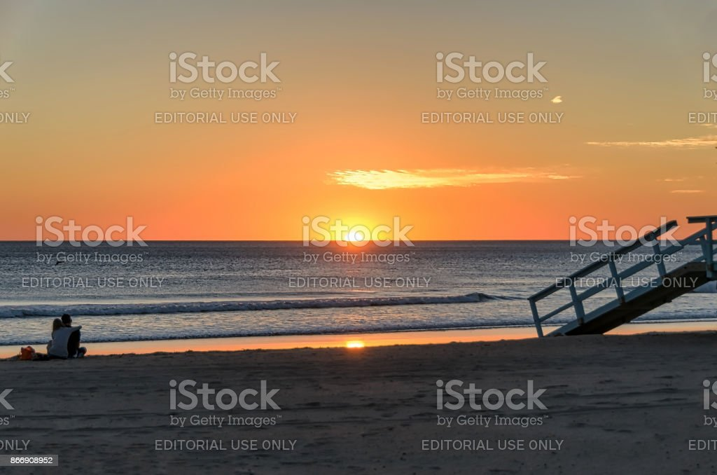 Silhouette of couple hugging watching sunset on the beach. stock photo