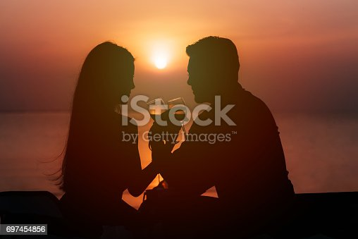 istock Silhouette of couple in love drinking wine during romantic dinner 697454856