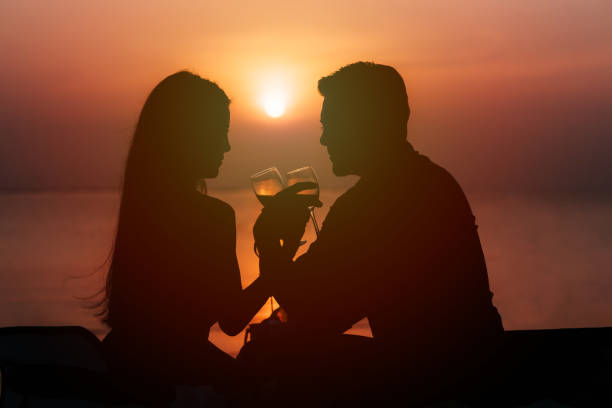 Silhouette of couple in love drinking wine during romantic dinner stock photo