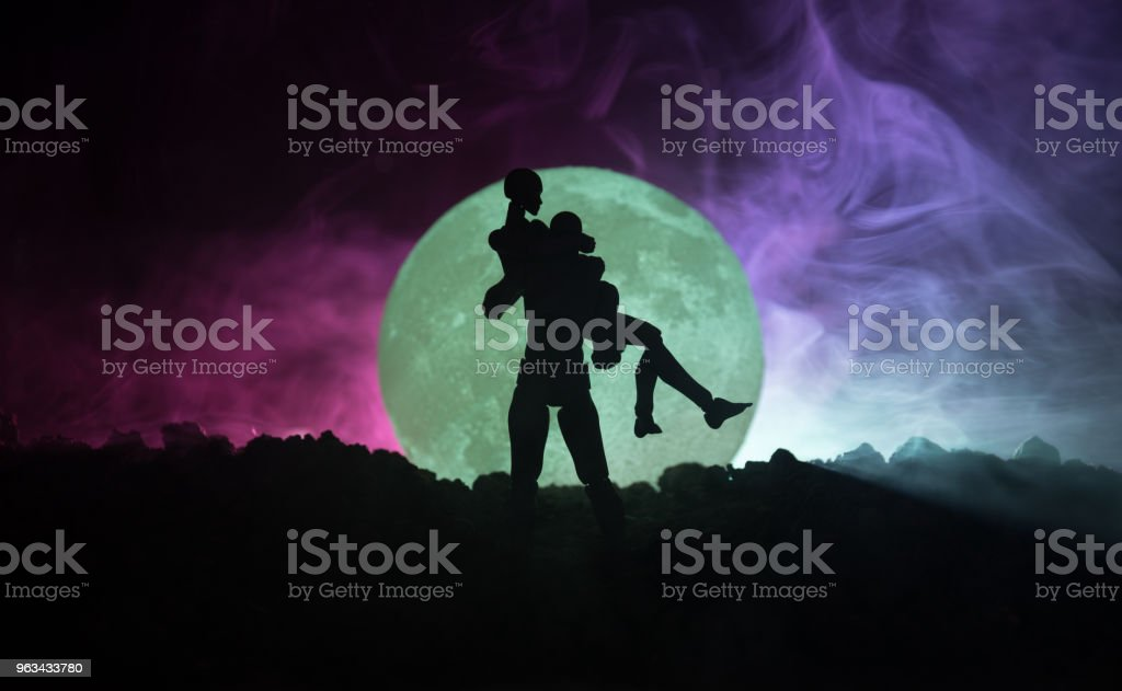 Silhouette of couple kissing under full moon. Guy kiss girl hand on full moon silhouette background. Valentine`s day decor concept. Silhouette of loving couple kissing against the moon - Zbiór zdjęć royalty-free (Azerbejdżan)