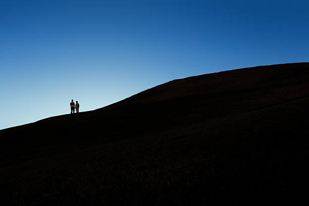 Silhouette of Couple on a Hill at Night stock photo