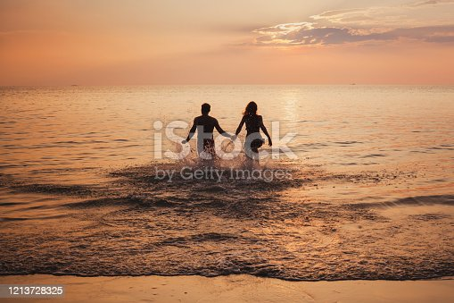 silhouette of couple on sea beach at sunset, happy holidays for two, man and woman holding hands and running to water