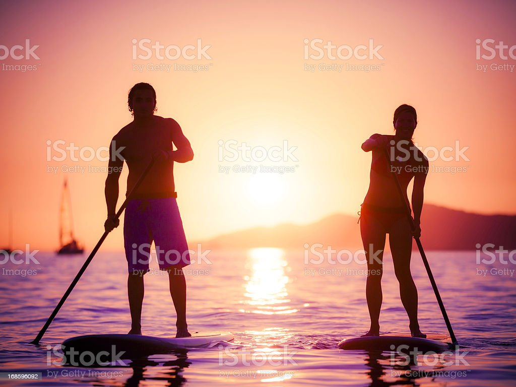 Silhouette of couple on stand-up paddle boards stock photo