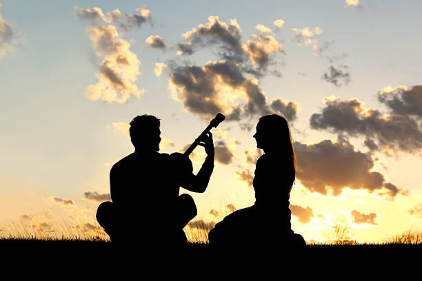 Silhouette of Couple Playing Guitar at Sunset A silhouette of a happy, young couple in love, with the man playing guitar for the woman isolated in front of a beautiful sunset in the sky. serenading stock pictures, royalty-free photos & images