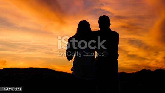 Silhouette of couple sitting under moody sky, hugging each other