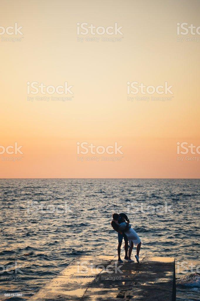 Silhouette du couple debout et s'embrasser sur la jetée, regarder le lever du soleil à l'heure d'été plage - Photo