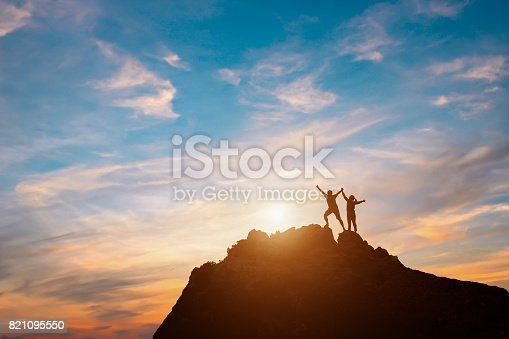 istock Silhouette of couple teamwork  hiker helping each other on top of mountain 821095550