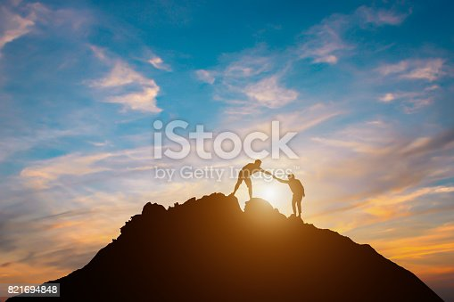 istock Silhouette of couple teamwork  hiker helping each other on top of mountain 821694848