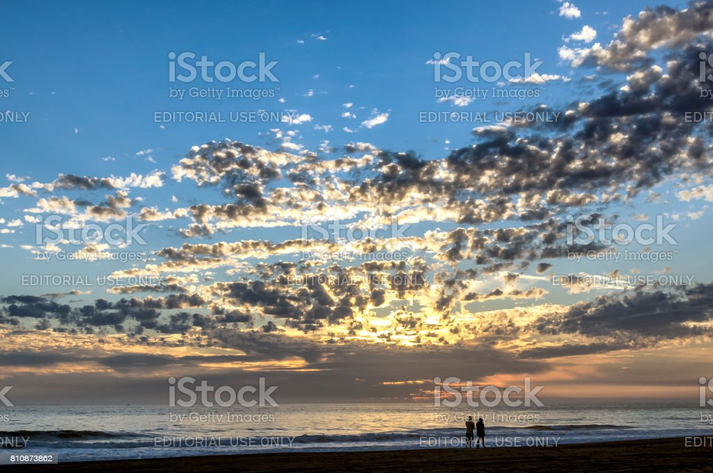 Silhouette of couple walking on California beach with sunset sky background stock photo