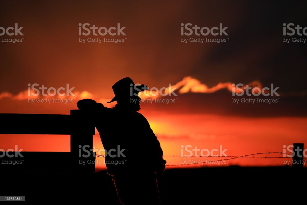Silhouette of Cowboy Leaning Against Wooden Post at Corral stock photo