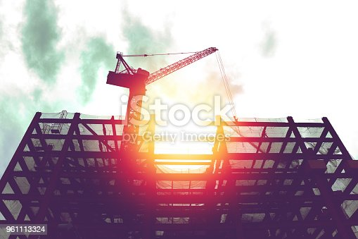 silhouette of crane in building construction site with sunlight and dark sky