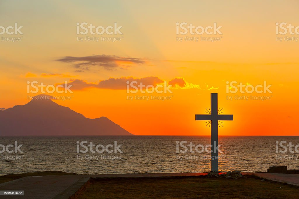 Silhouette of cross at sunrise or sunset with light rays stock photo