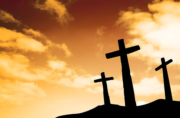Silhouette of crosses on a hill against orange sky stock photo