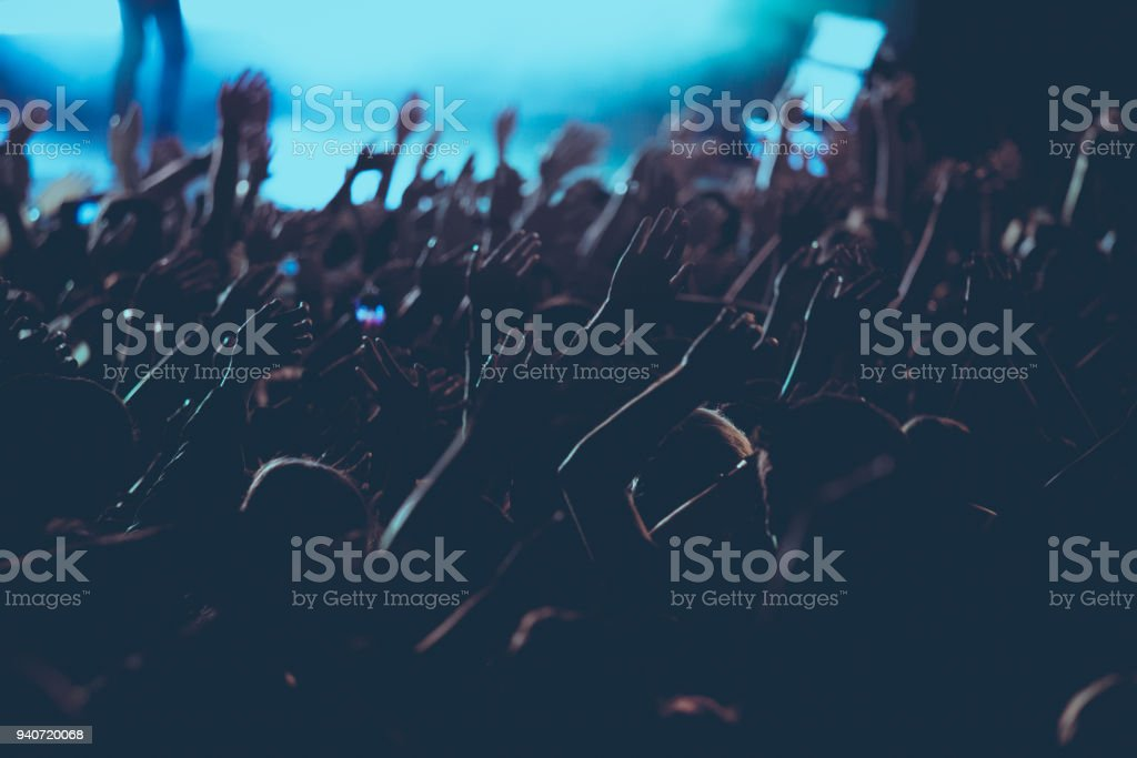 Crowd with hands in the air in live concert.