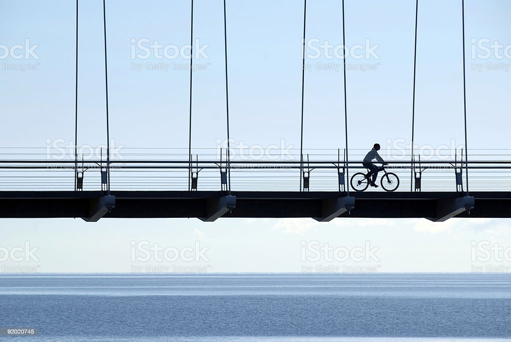 Silhouette of cyclist going through a cable bridge stock photo