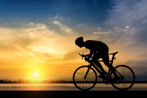 silhouette of cyclist on the background of beautiful sunset - cycling stock photos and pictures
