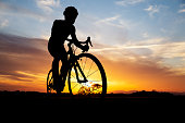 Double exposure of silhouette of cyclist riding in the field and orange sunset sky.