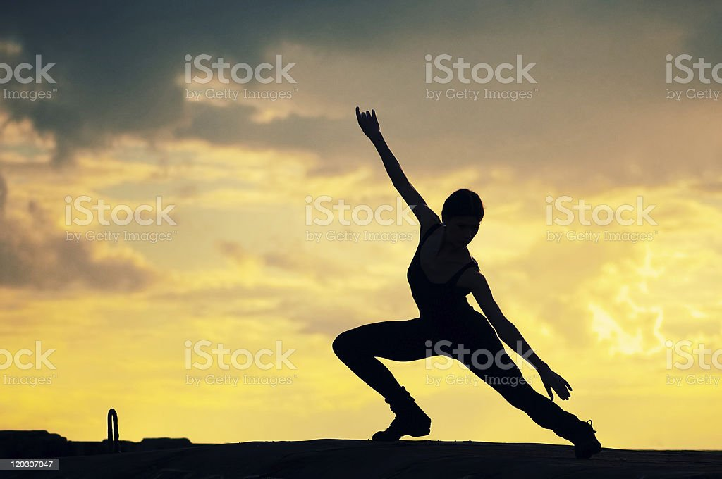 Silhouette of dancing woman over sunset. Yoga royalty-free stock photo