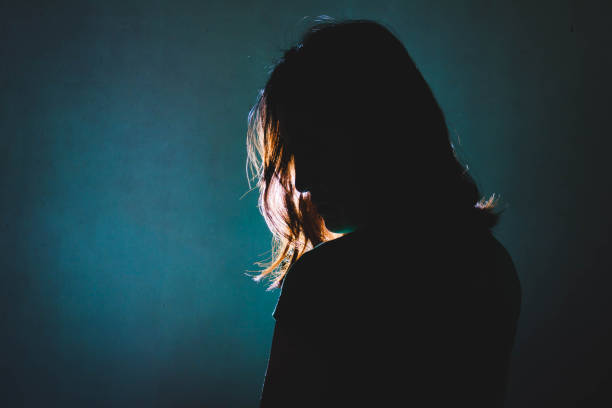 silhouette of depress woman standing in the dark with light shine behind stock photo