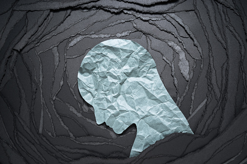 Negative emotion image. Person head shaped paper on black torn paper background.