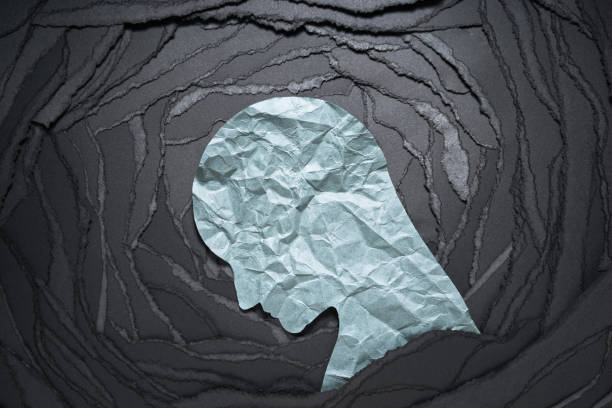 Silhouette of depressed and anxiety person head. Negative emotion image. Person head shaped paper on black torn paper background. suicide stock pictures, royalty-free photos & images