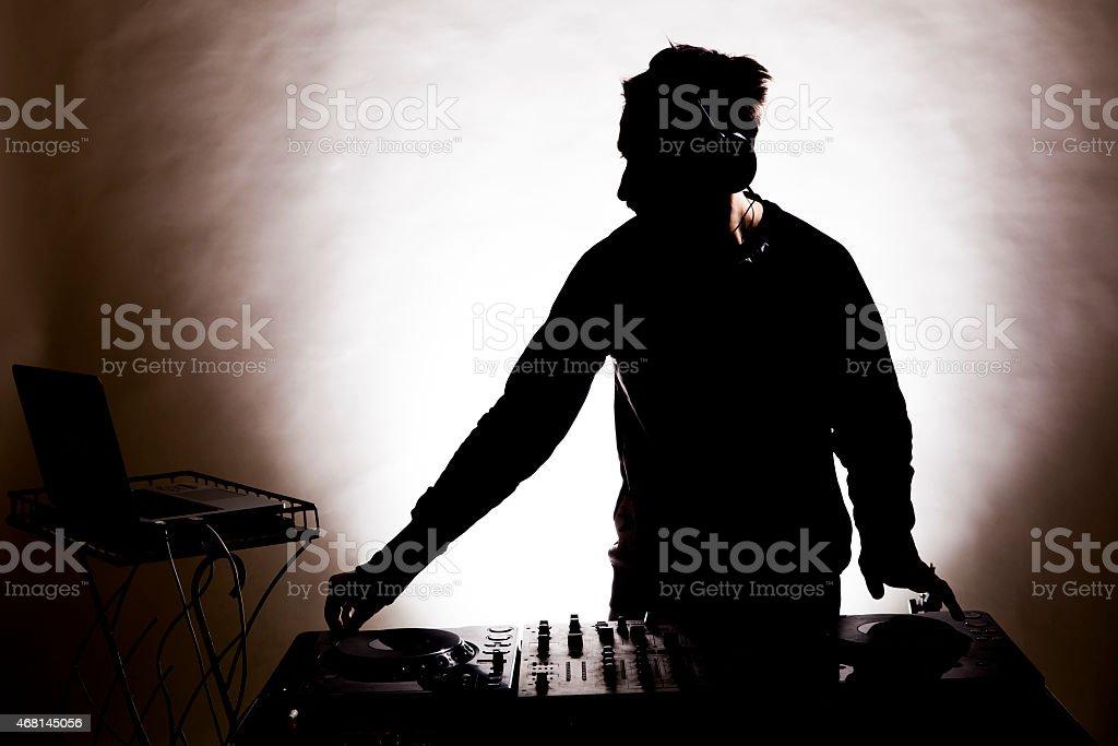 Silhouette of disc-jockey mixing music stock photo