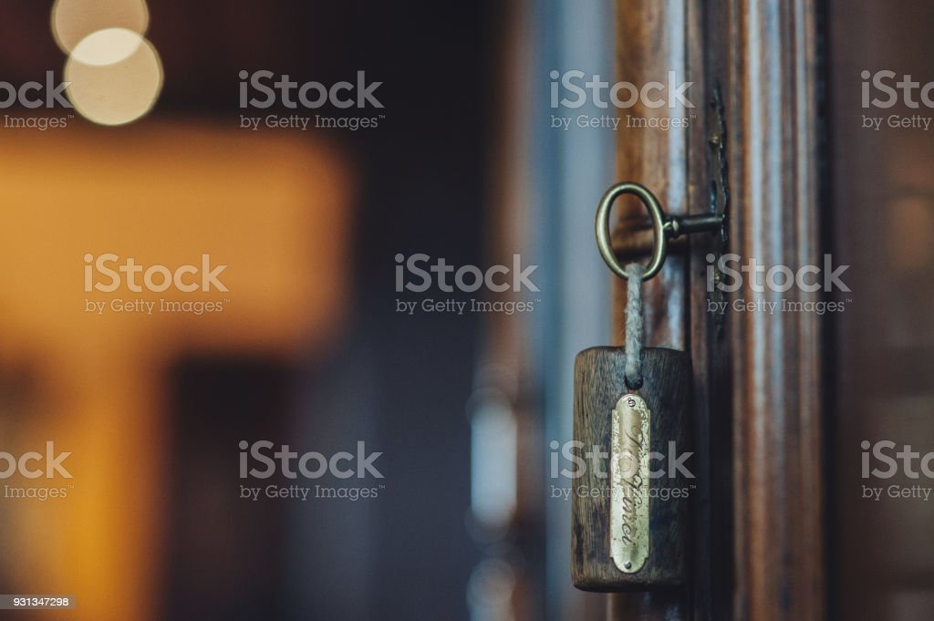 Silhouette of door keys hanging on the open door stock photo