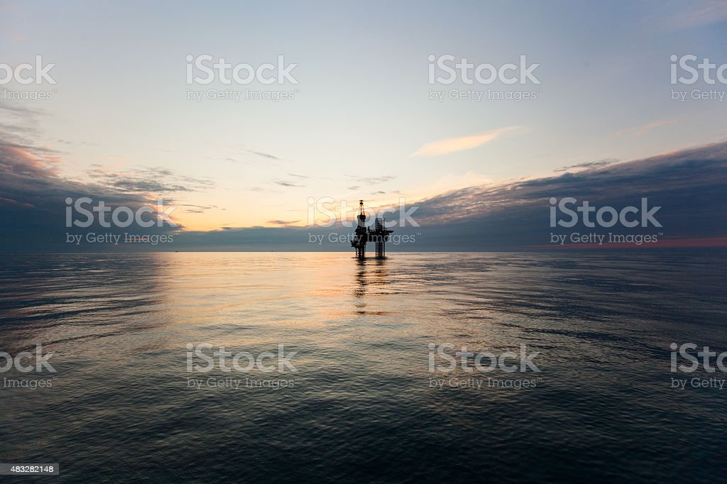 Silhouette of drilling rig at sunset stock photo