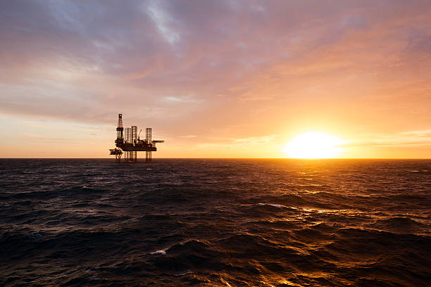 silhouette of drilling rig at sunset - construction platform stock pictures, royalty-free photos & images