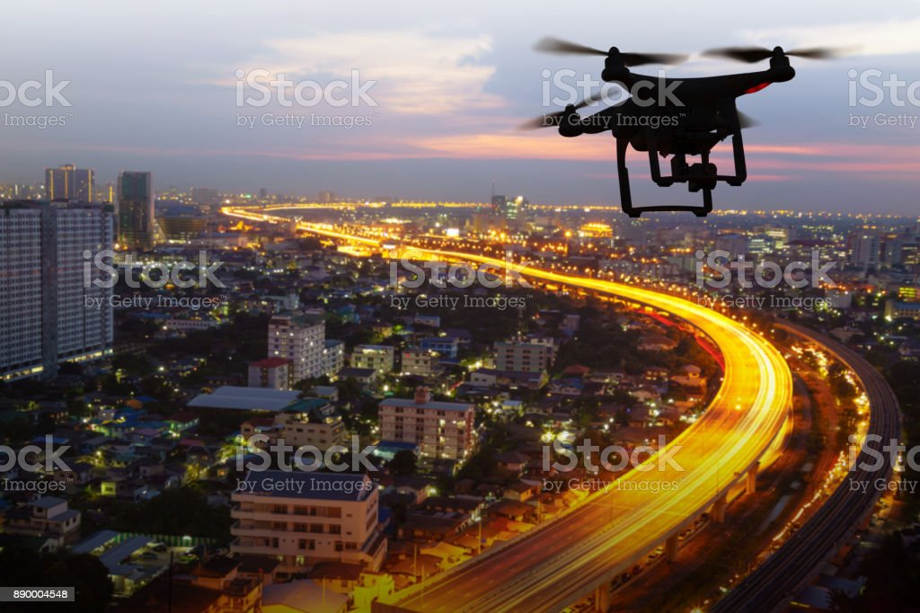 Silhouette of drone flying above city at sunset stock photo