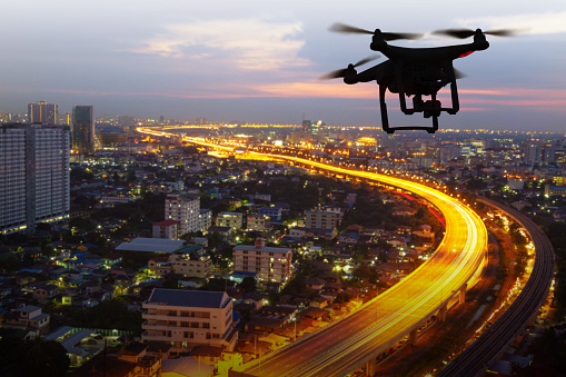 Silhouette Of Drone Flying Above City At Sunset Stock Photo - Download Image Now