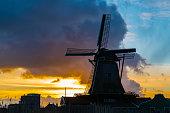 Silhouette of dutch windmill in the village of Zaanse Schans at sunset, Netherlands