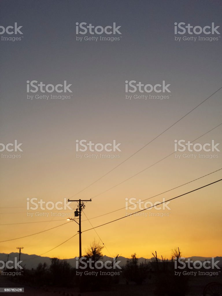 Silhouette of electricity poles and streetlamp under nightly desert sky stock photo