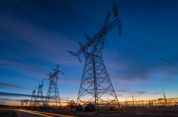 Silhouette of electricity pylons and high-voltage power lines at night