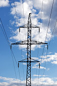 Silhouette of electricity transmission pylon on a background of blue sky