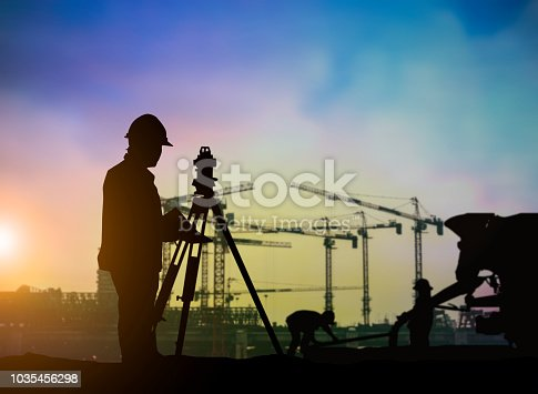 istock Silhouette of engineer and construction team working at site over blurred background for industry background with Light fair.Create from multiple reference images together. 1035456298
