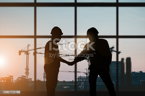 istock Silhouette of engineer and construction team working at site over blurred background for industry background with Light fair.Create from multiple reference images together 1050723768