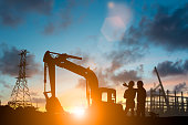 istock Silhouette of engineer and construction team working at site over blurred background for industry background with Light fair.Create from multiple reference images together 1050723782