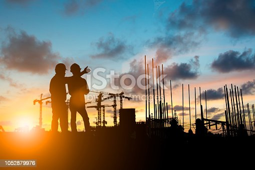 istock Silhouette of engineer and construction team working at site over blurred background for industry background with Light fair.Create from multiple reference images together 1052879976