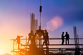 istock Silhouette of engineer and construction team working at site over blurred background for industry background with Light fair.Create from multiple reference images together 1052879982